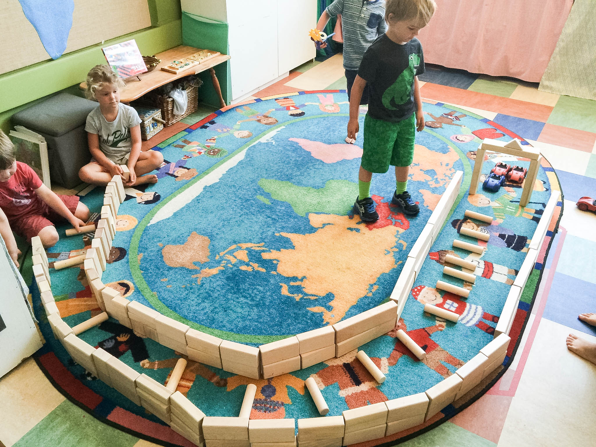 kids building with blocks on a rug