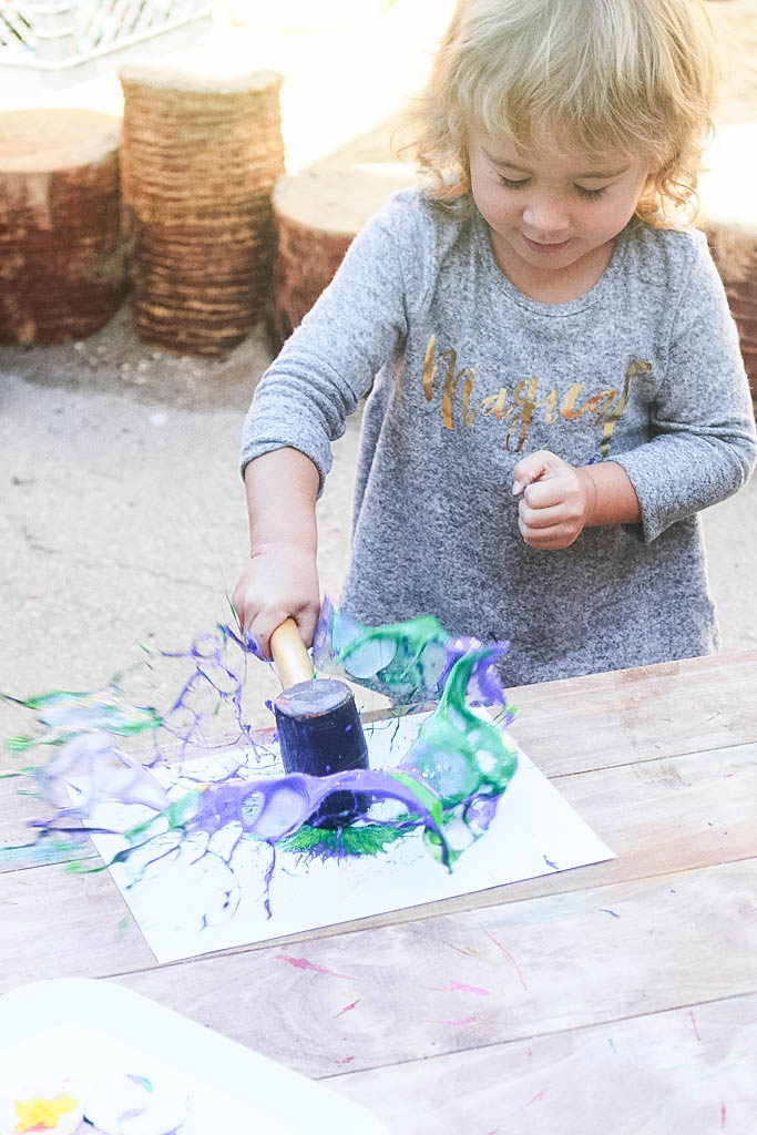 girl hitting paint with mallet