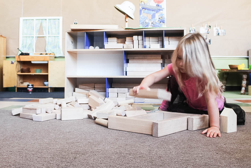 girl playing with blocks in a classroom